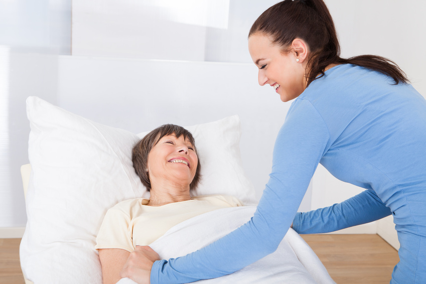 Caretaker Covering Senior Woman With Blanket